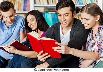 Students in library. Four cheerful students reading a book together while sitting against bookshelf in a library