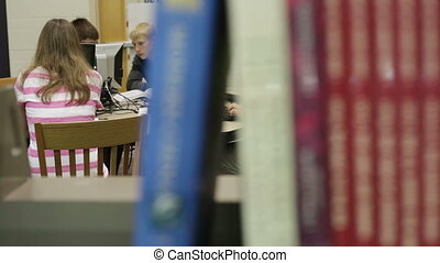 A group of students working & researching in the school library (media center)