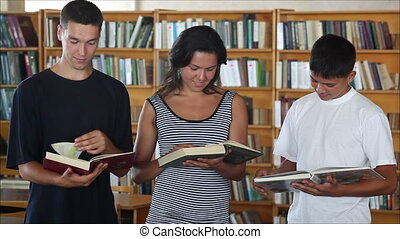 students in the library looking at camera and smiling