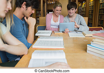 Students in the library studying with two using tablet pc