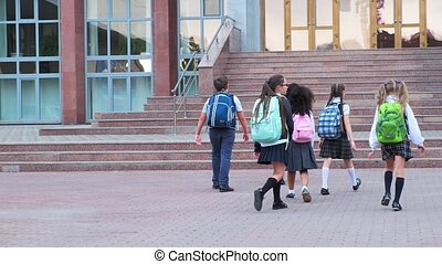 students in uniform walk to school building with stone steps...