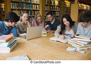 Students learning in a library - Students sitting at a table...