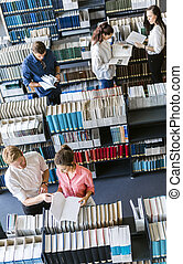 Students learning, reading in the library