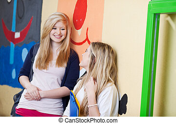Students Looking At Each Other While Leaning On School Wall