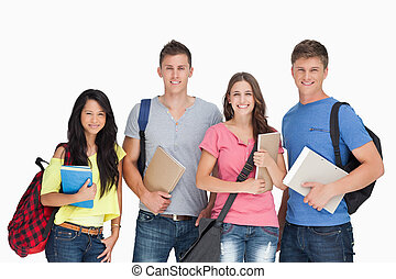 Students looking at the camera as they hold notepads