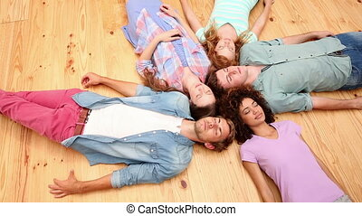 Students lying on floor in a circle