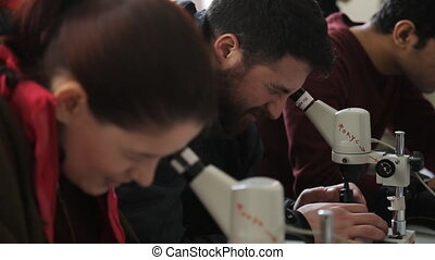Students on practical training with optical microscopes look in eyepieces, woman tries to remove result on phone.