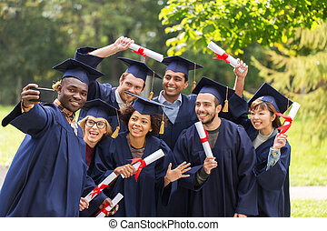 students or graduates with diplomas taking selfie -...