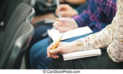 Students participating in a lecture and taking notes -...