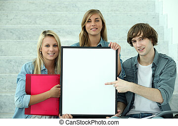 Students pointing at white board