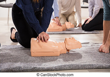 Students Practicing CPR Chest Compression On Dummy