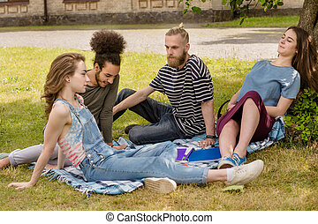 Students relaxing on grass.