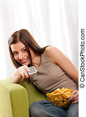 Students series - Smiling young woman watching television and ea