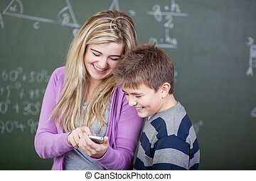 Students sharing a joke in the classroom with cellphone