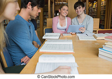Students sitting at library table smiling while holding a tablet pc in college