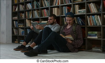 Students sitting in front of a bookshelf talking