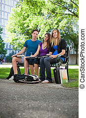 Students sitting on campus bench