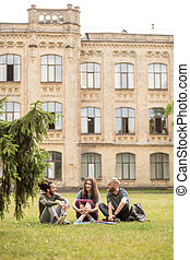 Students smiling and talking sitting on grass.