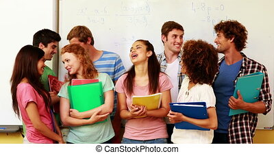 Students standing in classroom givi