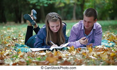 Students studying in autumn park