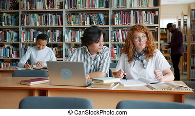 Students studying in library talking using laptop doing research together