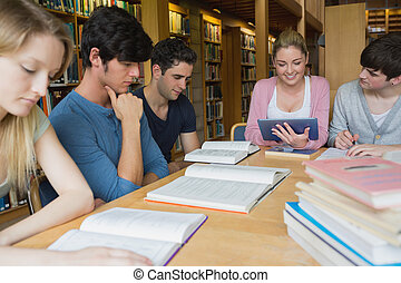 Students studying together in library with one using a tablet pc in college