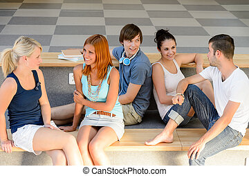 Students talking sitting on school bench