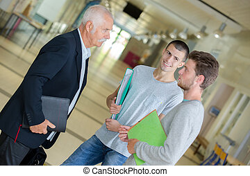 Students talking to teacher in lobby