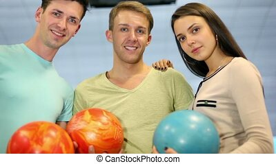 Students team hold bowling balls and smile, closeup view