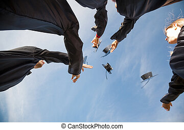 Students Throwing Mortar Boards In Air On Graduation Day -...