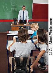 Students Using Digital Tablet At Desk