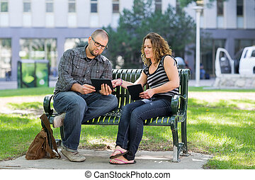 Students Using Digital Tablet On Bench At Campus