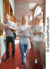 Students walking through hallway toward camera in school