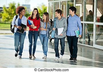 Students Walking Together On College Campus - Full length of...