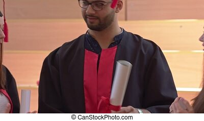 Students wearing graduation gown talking and joking. -...
