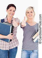 Students with books and thumbs up
