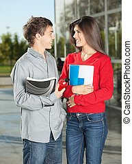Students With Books Looking At Each Other On Campus