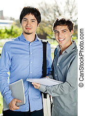 Students With Books Standing On College Campus