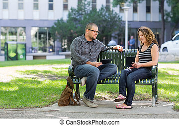 Students With Digital Tablets Sitting On Bench At Campus