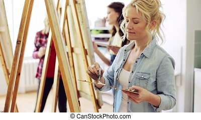students with easels painting at art school - art school,...