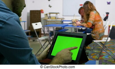 Students with green screen tablet pc waiting for teacher in classroom
