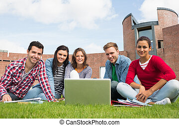 Students with laptop in the lawn against college building