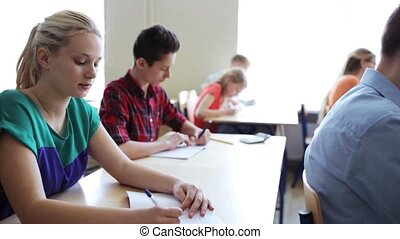 students with notebooks writing test at school