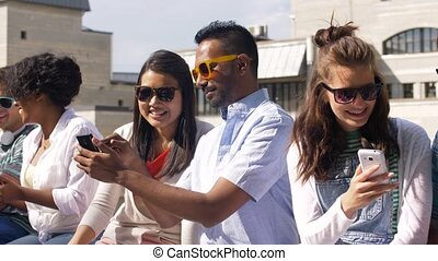 students with smartphones and tablet pc in city