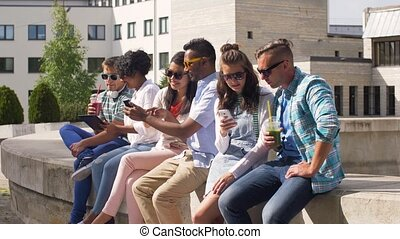 students with smartphones and tablet pc in city -...