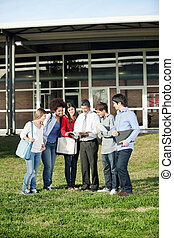 Students With Teacher Discussing Over Book On Campus