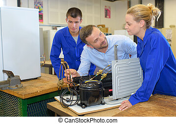 Students with teacher looking at heating element