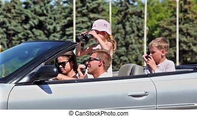 Students with two kids sit in cabriolet, boys talk by hand radio transmitter and little girl looks around through binocular at sunny summer day