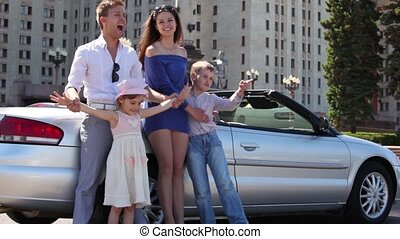 Students with two kids stand near cabriolet, then boy take...