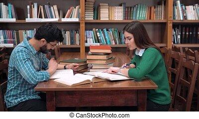 Two smart students working on home assignment, reading books attentively, sitting at square library table next to the bookshelves, curious girl pointing at the text in boy's book